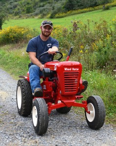 Dayton Spackman, a 2013 graduate of Penn State University, drives his restored 1964 Wheelhorse 854 on his family farm, located in Port Matilda, Pa., on Wednesday evening. Spackman restored the tractor for use to teach his daughter how to drive tractors.